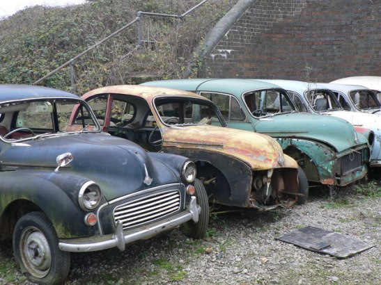 Without the MOT that makes it legal to drive a car, they heavily diminish in value, leaving such cars in a graveyard. (Photo thanks to Steve Thompson, found here: http://www.geograph.org.uk/photo/1680344)